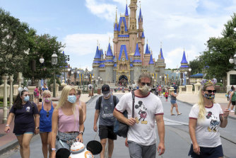 Guests wear masks as required at the Magic Kingdom at Walt Disney World in Florida.