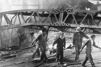 Westgate Bridge collapse, 1970: A victim is carried from a massive pile of twisted girders by civil defence men and workmates.