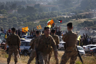 Hezbollah supporters wave their group, Iranian and Palestinian flags, in solidarity with Palestinians on the Lebanese-Israeli border near the Israeli settlement of Metula, background.