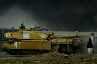 An Iraqi man stands in front of a British tank on the road from Basra to Baghdad in 2003.