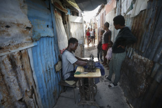 Poverty is fuelling discontent on the streets of Port-au-Prince, Haiti. Charles Lewis, 25, is pictured here repairing clothes.