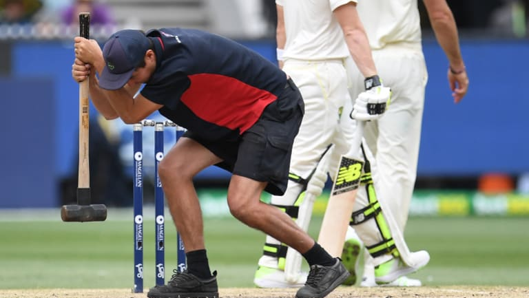 A groundsman tries to hammer some sense into the Boxing Day Test pitch.