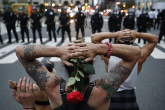 Protesters kneel in front of New York City Police Department officers.