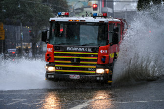 A fire truck travels through deep water caused by Melbourne's rain on Friday.
