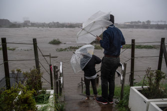 People look at the flooded Tama River during Typhoon Hagibis on October 12