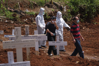 A family at the grave of their relative who died of coronavirus in one of the two official cemeteries for COVID-19 victims in Jakarta, Indonesia.