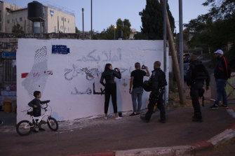 """Palestinian activists are approached by Israeli police as they repair a mural defaced by an Israeli settler.  The male activist  was arrested after repainting the Arabic phrase """"welcome to the steadfast neighbourhood of Sheikh Jarrah""""."""
