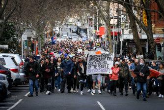 Anti-lockdown protesters march through Melbourne's CBD on Saturday.