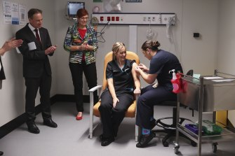 Minister for Health and Aged Care Greg Hunt and ACT Minister for Health Rachel Stephen-Smith observe as COVID testing nurse Maddy Williams receives the first COVID-19 vaccination in the ACT.