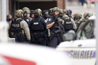 Police stand guard outside a King Soopers supermarket where a mass shooting took place.