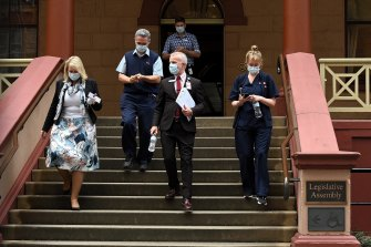 Members of NSW health leave NSW Parliament House which was suspended after NSW Agriculture Minister Adam Marshall tested positive for COVID-19 in June.