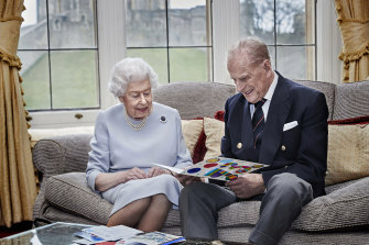 Well wishes: the Queen and Prince Philip read a homemade wedding anniversary card, given to them by their great grandchildren.