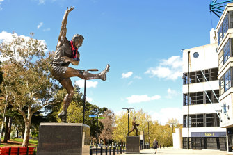 A Demons scarf is draped around the statue of Barassi outside the MCG.