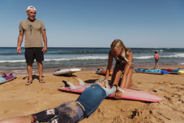 Nick Carroll watches as Newport's Nina Lindley, 15, demonstrates a technique on Dylan Wilkinson so surfers can easily flip someone on to a board in an emergency.