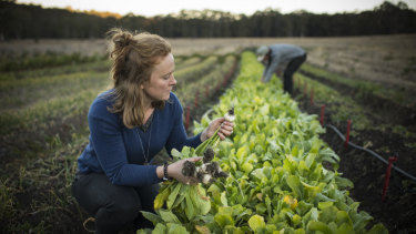 Erika Watson inspects some of the  organically grown vegetables on their property.