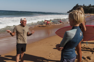 Nick Carroll instructs local surfers Nina Lindley and Dylan Wilkinson on Newport Beach.