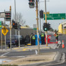 Police at the Mickleham Road pedestrian lights near the entry ramp to the Tullamarine Freeway where a woman was believed to have been crossing when she was struck and killed.