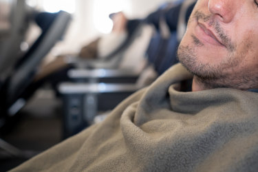 Man sleeping on plane under blanket