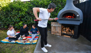 Chef Gianluca Bocci tends to his beloved wood-fire pizza oven as his wife Sandra and their daughters Chloe (13) Astrid (11) laugh nearby.