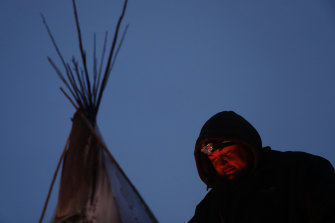 James Logan, a Northern Arapaho Native American from Wyoming, sits by a fire at the Oceti Sakowin camp where people have gathered to protest against the Dakota Access oil pipeline in Cannon Ball, North Dakota, over the past four years.
