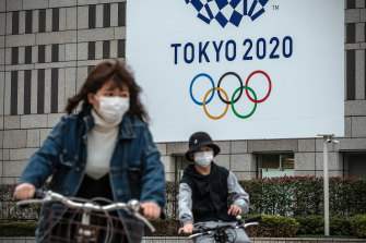 People cycle past a banner for the Tokyo Olympics on March 13, 2020 in Tokyo, Japan.
