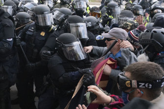 Capitol police officers in riot gear push back demonstrators who try to break a door of the US Capitol on January 6.