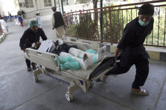 An injured man is carried into a hospital after a car bomb explosion in Kabul.