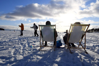People sit in the sun in Helsinki, Finland, which has yet again been named the happiest country in the world.