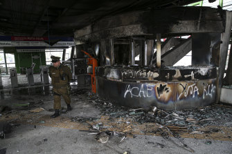A police officer walks in a subway station that was torched during the protests in Santiago.