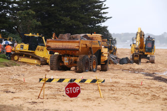 Earthmoving equipment moves boulders to create a sea wall to protect damaged houses at Wamberal on Sunday.