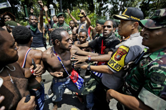 Papuan protesters scuffle with police and soldiers near the presidential palace in Jakarta on August 22, 2019.
