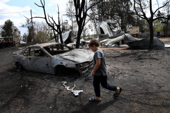 Eight year-old Jarrod McInnes walks next to the remains of a house that his family was about to buy and was destroyed by bushfires in Rappville, NSW in October.