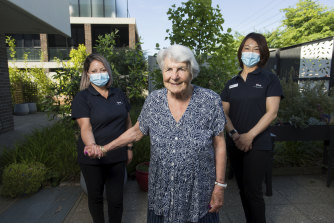 Louise Mathers and Mitsu Kamo lend a hand to Regis Aged Care resident Jean Sarsby.