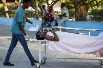A medical worker pushes the stretcher of a civilian man wounded in an attack on the Afrik hotel in Mogadishu, Somalia, on Sunday.