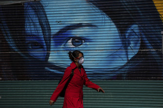 A woman walks past a shuttered fashion boutique in downtown Mexico City.
