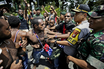 Papuan activists scuffle with police and soldiers near the presidential palace in Jakarta, in 2019, following the unrest at Surabaya.