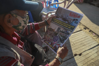 A man reads at a newspaper, which reports on the military coup, in Yangon, Myanmar on Tuesday.