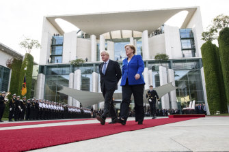 Germany's Chancellor Angela Merkel and British Prime Minister Boris Johnson walk the red carpet during a welcome ceremony in Berlin.