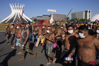 Indigenous people march past the Brasilia Cathedral. Activists travelled to the capital to press for an end to illegal mining and logging on their land and oppose a bill they say would limit recognition of tribal lands.