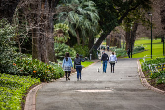 People enjoying a walk in the Fitzroy Gardens on Monday