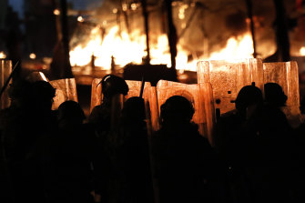 Riot police watch the flames rise from a tent city set up by protesters. The tents were set on fire by men who appeared to be civilians, however they were accused of being members of a private unit of the parliamentary guards.