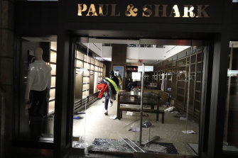 A man carries merchandise out of a store that was broken into in New York.