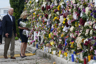 President Joe Biden and first lady Jill Biden visit memorial wall covered in flowers and photos of the missing.