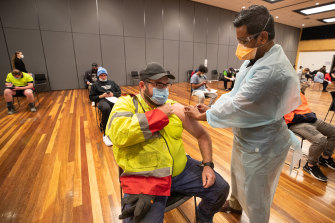 Warehouse worker Daniel Matcham rolls up his sleeve to get jabbed at a clinic in Hoppers Crossing.