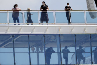 People wearing protective masks look out from the Coral Princess cruise ship while docked at Port Miami on Saturday.