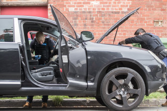 Police search a car parked on Lalor Street, Port Melbourne during the raid.