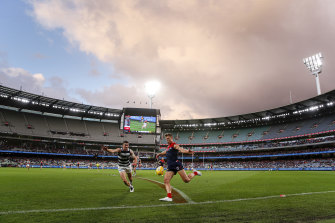 Jake Melksham gets a kick away for the Demons on a wet and wintry afternoon at the MCG.