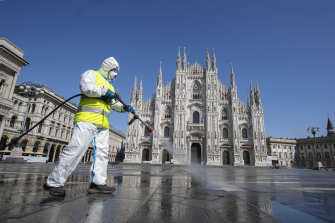 A worker sprays disinfectant to sanitise Duomo square in Milan, Italy in March.
