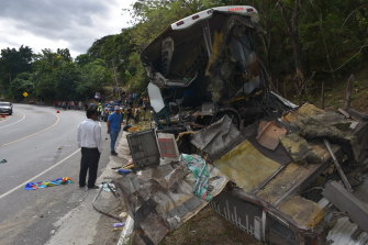 The wreckage of a passenger bus that was involved in a collision with a trailer truck lies on the side of the highway in Gualan in Guatemala.