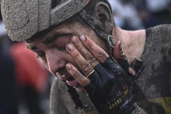 Belgian superstar Wout van Aert wipes mud from his eyes after the race that conditions made treacherous.